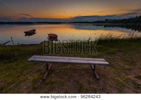 Beautiful Lake Sunset With Bench On Shore And Fisherman Boat