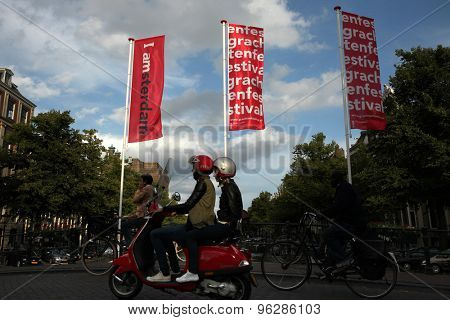 AMSTERDAM, NETHERLANDS - AUGUST 9, 2012: Two people drive on a Vespa scooter over the bridge decorated with banners with an official brand of the city in Amsterdam, Netherlands.