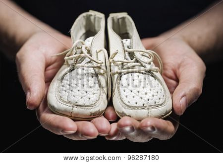 Man holding old worn white baby shoes in his hands.