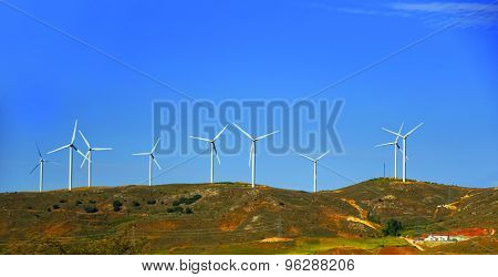 Wind Turbines On The Hill In Front Of Blue Sky