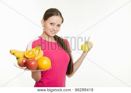 Girl Athlete Holding A Plate Of Fruit And Dumbbell