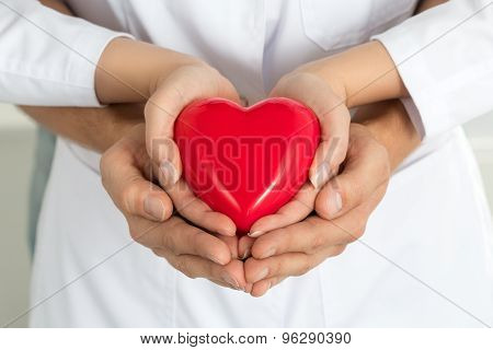 Woman's And Man's Hands Holding Red Heart Together