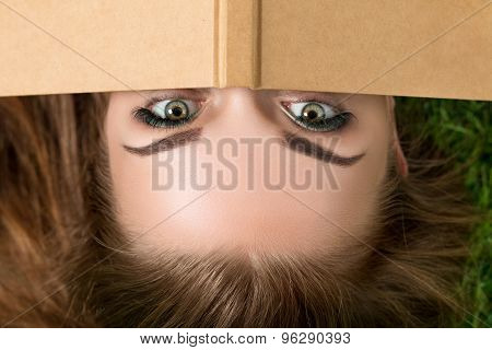 Beautiful Young Woman Hiding Her Face Behind Book Cover