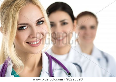 Portrait Of Young Blonde Female Doctor Surrounded By Medical Team