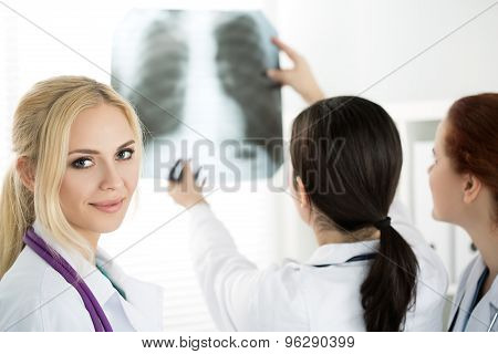 Female Medicine Doctor With Two Colleagues Looking At X-ray Picture