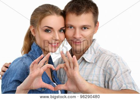 Portrait Of Smiling Beautiful Girl And Her Boyfriend Making Shape Of Heart