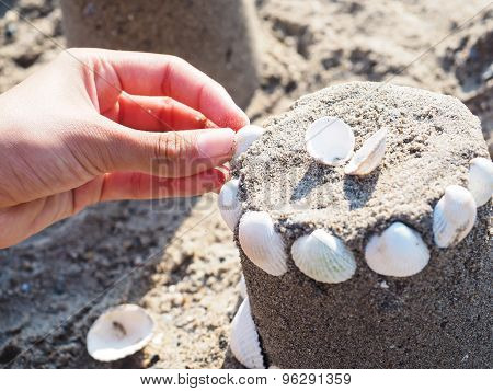 Person Creating A Sand Castle With White Clams