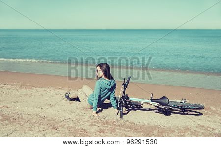 Girl With A Bicycle Sitting On Beach