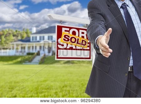 Real Estate Agent Reaches for Handshake with Sold Sign and New House Behind.