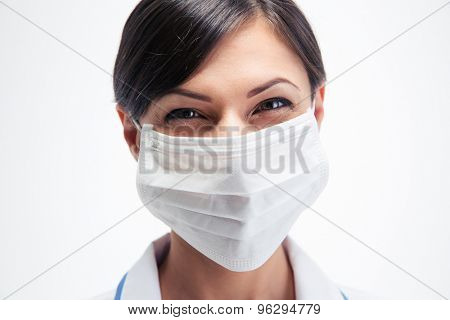 Happy female medical doctor in mask looking at camera isolated on a white background