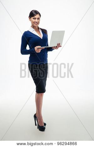 Full length portrait of a smiling businesswoman standing with laptop and looking at camera isolated on a white background