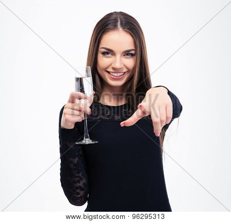 Happy woman holding glass with champagne and pointing finger at camera isolated on a white background