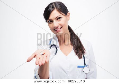 Smiling female doctor holding medication isolated on a white background. Looking at camera