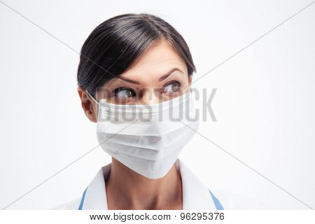 Female medical doctor in mask looking away isolated on a white background
