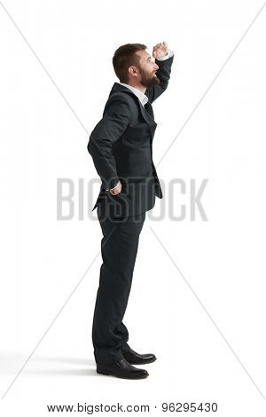 smiley businessman holding his hand near brow and looking up. isolated on white background