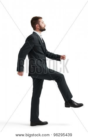 serious businessman in formal wear raised one leg like climbing stairs and looking forward. isolated on white background