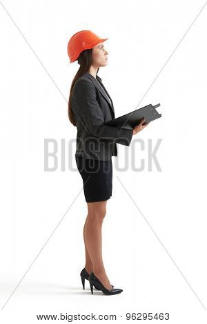 sideview full length portrait of serious businesswoman in orange hardhat looking up. isolated on white background