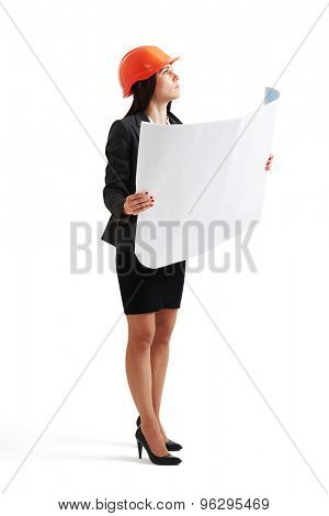 serious woman in hardhat holding blueprint and looking up. isolated on white background