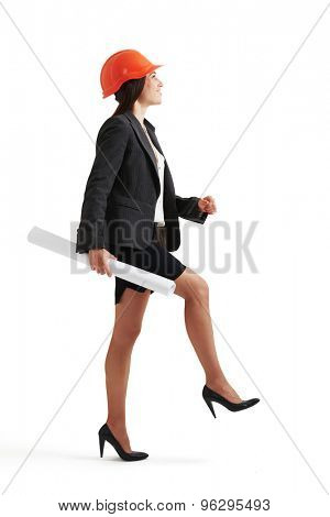 smiley constructor woman in formal wear with blueprint in one hand doing one step and looking forward. isolated on white background