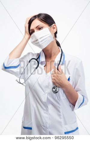 Portrait of female medical doctor in mask having headache over white background