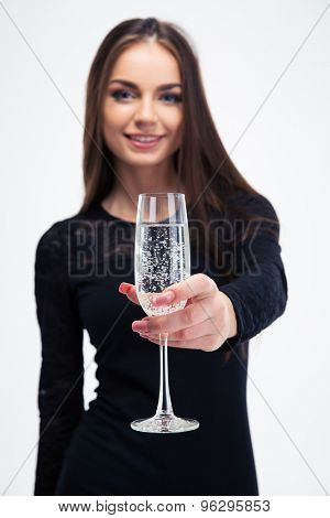 Happy young woman holding glass with champagne isolated on a white background. Looking at camera. Focus on glass