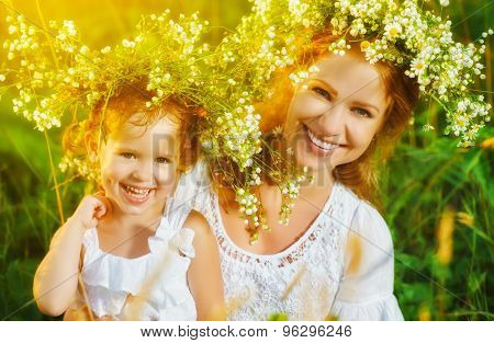 Happy Laughing Daughter Hugging Mother In Wreaths Of Summer Flowers