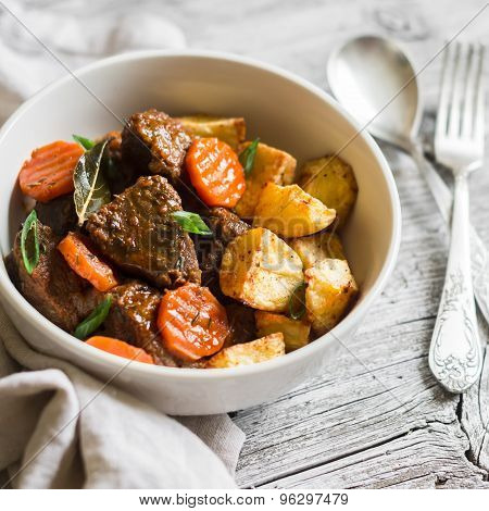 Beef Goulash With Carrots And Roasted Potatoes In A White Bowl On A Light Wooden Background