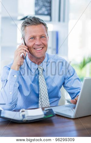 Serious businessman having phone call in office