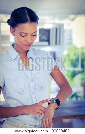 Serious businesswoman using her smart watch in office