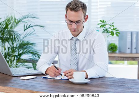 Concentrated businessman writing on a notebook at office