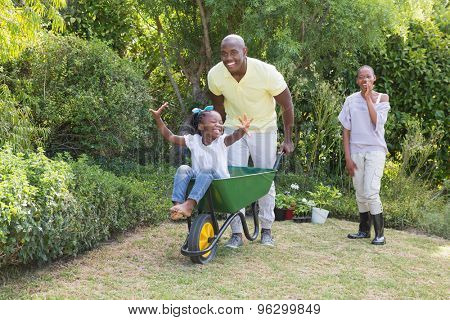 Happy smiling couple playing with wheelbarrow and their daughter at home in garden