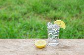 foto of vodka  - Vodka with lemon on wooden table background - JPG