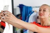image of antidepressant  - Blonde woman standing near wardrobe rack full of clothes and mirror making selfie with cellphone in new dress - JPG