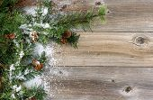 pic of snow border  - Christmas border with rough evergreen fir branches cones and snow on rustic wooden boards - JPG