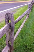 image of pastures  - Split rail fence at edge of grassy pasture meets up with blacktop road - JPG