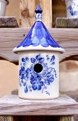 stock photo of peddlers  - Ceramic birdhouse with ornate blue and white designs - JPG