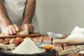 stock photo of raw materials  - A handful of flour with egg on a rustic kitchen - JPG