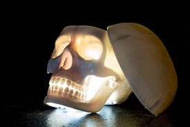 stock photo of eye-sockets  - Skull with glowing eyes and mouth in the dark - JPG
