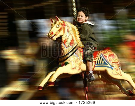 Excited Little Boy On Fast Moving Carousel With Wind In Hair