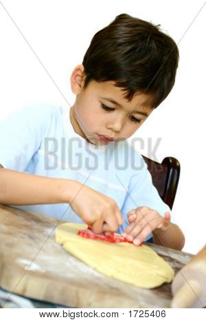 Boy Using Cookie Cutter On Cookie Dough