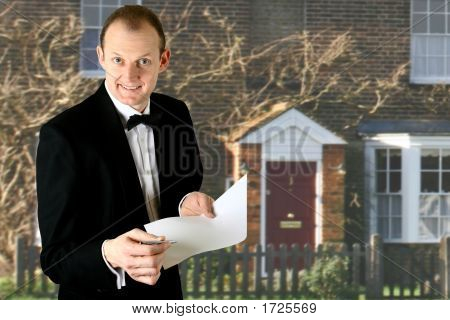 Caucasian Housing Agent With House In Background