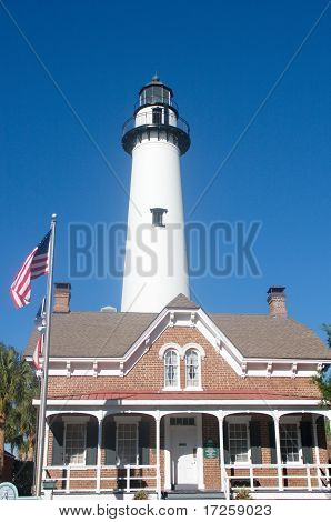 White Lighthouse Behind Brick House With American Flag