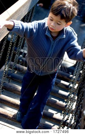 Young Boy Walking Across Wooden Bridge At Playground