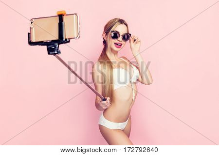 Attractive woman posing for selfie wearing white underwear. Horizontal studio shot.