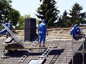 stock photo of roof tile  - three men on a roof tiling - JPG