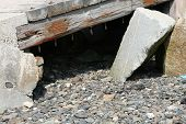 picture of fieldstone-wall  - Old railway sleeper lying over broken stones and shale - JPG