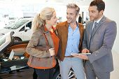 Car seller with couple in car dealership poster