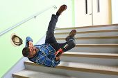 Hispanic worker falling on stairs while holding cordless drill poster