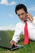 Businessman Using Laptop Outdoors poster