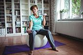 Senior woman exercising with dumbbells on exercise ball at home poster